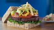 Una hamburguesa sobre un pan de granos integrales con lechuga, tomate, salsa de maíz, aguacate y nachos