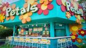 """Um quiosque com um bar, cadeiras e uma placa em que se lê """"Petals"""""""