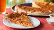 Una porción de pizza junto a una pizza, un plato de queso parmesano y un plato de hojuelas de pimiento rojo