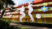 """Figuras gigantes de un hombre y una mujer bailando el """"twist"""" adornan una cara de Disney's Pop Century Resort"""