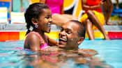 Padre e hija se ríen en la piscina de Disney's Pop Century Resort