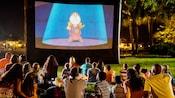 Um grupo de visitantes reunido em um jardim para assistir à projeção de um filme da Disney