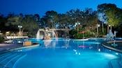 Una piscina iluminada ofrece una fuente decorada que brilla bajo el cielo iluminado por la luna de Florida