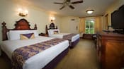 Dos camas Queen con cabeceras de madera decoradas junto a la mesa lateral, frente al vestidor, TV, 2sillas y un espejo