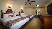 Dos camas Queen y una mesa lateral frente al vestidor, TV, espejo y 2sillas más un ventilador de techo