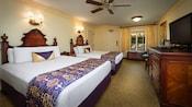 Dos camas Queen con cabeceras de madera junto a la mesa lateral, frente al vestidor, TV, 2sillas y un espejo