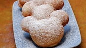 Beignets shaped like Mickey Mouse topped with powdered sugar