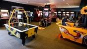 Juegos de hockey de mesa, baloncesto y de carreras de autos en una sala de videojuegos en Disney's Saratoga Springs Resort & Spa