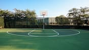 A basketball hoop in a large fenced green court