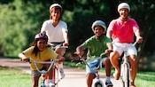 Una familia de 4 pasean en sus bicicletas con cascos por un sendero bordeado de árboles