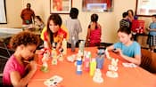 Un miembro del elenco observa a 2 niños pintando figuras de Disney en una mesa de manualidades