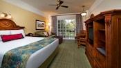 Un grand lit avec une table de nuit et un canapé avec un pouf face à une commode