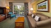 Un canapé avec table basse face à un centre de divertissement près d'une fenêtre de balcon avec rideaux