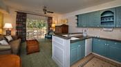 Une cuisine avec évier et cafetière sur un comptoir près du salon