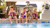 4 niñas con trajes de baño de The Little Mermaid sentadas en el borde de la piscina, que se ríen y salpican agua