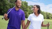 Un hombre y una mujer caminan por el campo de golf, cada uno con un palo de golf