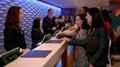 Miembros del Elenco ayudan a Huéspedes en el mostrador del Concierge en el lobby