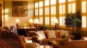 Un bureau, des canapés et des chaises dans un coin salon ensoleillé à côté d'une rangée de fenêtres