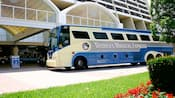 Side view of Disney's Magical Express bus parked outside a building