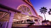A Monorail glides out of a station that's lit in a purple hue