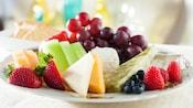 Um prato com vários tipos de queijos harmonizados com morangos, mirtilos, fatias de melão, uvas e framboesas