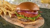 Um cheesebúrguer com um hambúrguer de carne bovina, bacon, alface, fatias de tomate, cebola e queijo cheddar, perto de uma pilha de batata frita