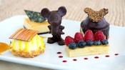 Une pâtisserie garnie de bleuets et de framboises près d'une pâtisserie recouverte de chocolat, une pâtisserie ronde garnie de chocolat, une pâtisserie triangulaire et une figurine de Mickey Mouse en chocolat