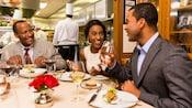 3personnes mangent et boivent à une table près d'une cuisine avec 4chefs à l'intérieur
