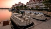 Two Sun Tracker® pontoon boats docked alongside Disney's Grand Floridian Resort & Spa