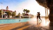 Um homem e uma mulher desfrutam da cachoeira da Beach Pool no Disney's Grand Floridian Resort & Spa