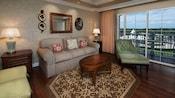 Una sala de estar amueblada con un sofá, mesa ratona, sillón y 3 otomanas, con un balcón con vista