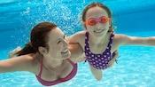 Une mère nage sous l'eau avec sa fille portant des lunettes de natation