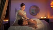 A masseuse at Senses – A Disney Spa massages the back of a woman who's lying on her stomach