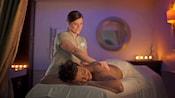 Une masseuse à Senses - A Disney Spa masse le dos d'une femme allongée sur le ventre
