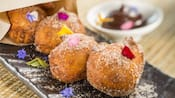 4 sugar dusted donut holes next to a dish of chocolate pudding