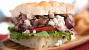 Um sanduíche recheado com cebola caramelada, rosbife, blue cheese, fatias de tomate e alface