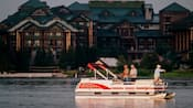 Um barco na água com 3 homens pescando em frente ao Wilderness Lodge Resort