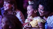 Uma garota sorridente usando uma roupa de Princesa da Disney sentada no colo da mãe