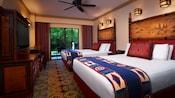 2 camas, mesa de canto, castiçais, ventilador de teto, mesa de madeira, cadeiras, TV, gaveteiro e vista do pátio para a floresta