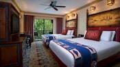 2 camas, lámparas de pared, mesa auxiliar, mesa de madera, sillas, cajones, TV, ventilador de techo y vista del patio al jardín
