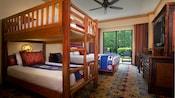 Litera con escalera, mesa auxiliar, ventilador, cajones, TV, sillas, mesa de madera y vista al bosque