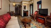 Sofá com almofadas, gaveteiro, TV, mesas de madeira, janela, cadeiras, espelho de parede e pia