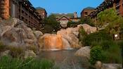 Un ruisseau dont l'eau se déverse dans une piscine entourée de rochers dans la cour du Disney'sWildernessLodge