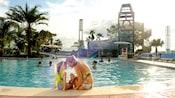 Une mère et sa fille assises au bord de la piscine BayCove de BayLakeTower à l'hôtel Disney'sContemporaryResort