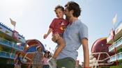 A father carries is young son through the courtyard of Disney's All Star Sports Resort as his wife and daughter trail behind