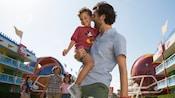 Un père transporte son jeune fils dans la cour du Disney's All Star Sports Resort alors que sa femme et sa fille les suivent