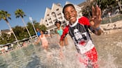 A smiling young boy enjoys pool time with his parents and sister at their Disney's Yacht Club Resort