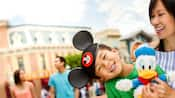 Young boy holds onto Donald Duck toy in Main-street USA at Disney Land Resort
