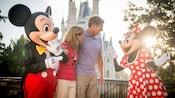 Un couple d'âge moyen devant le Cinderella Castle bavarde avec Mickey Mouse et Minnie Mouse