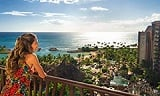 A woman on a balcony overlooking Aulani and the beach